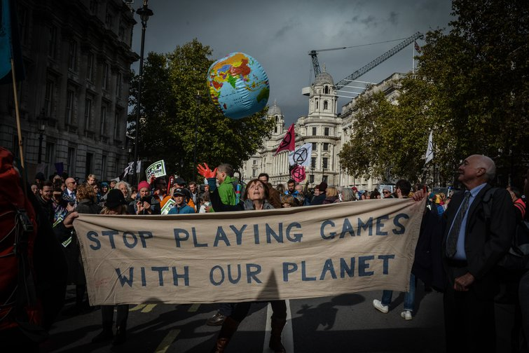 "Climate activists holding a banner reading ""Stop playing games with our planet"""