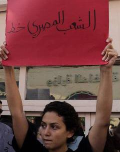 Young woman holding a banner with Arabic text on it