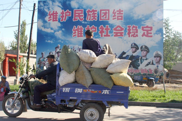 Motorcycle pick-up loaded with sacks driving in front of a poster with Chinese lettering on it