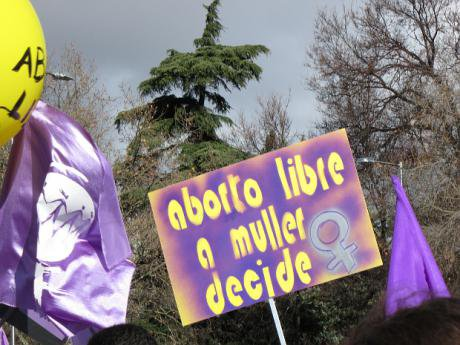 Protest banners, one saying 'aborto libre a muller decide'