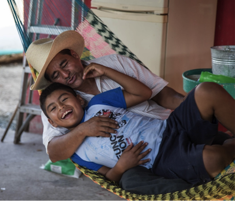 Rubicel Lopez shares a moment of levity with his boy at his home near the site of the well explosion. Author's photo.