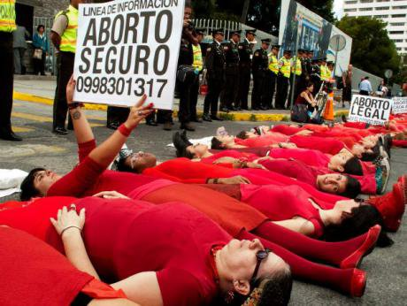 Women dressed in red lying in the street