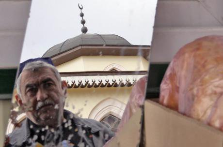 An older Tatar man in front of a mosque.