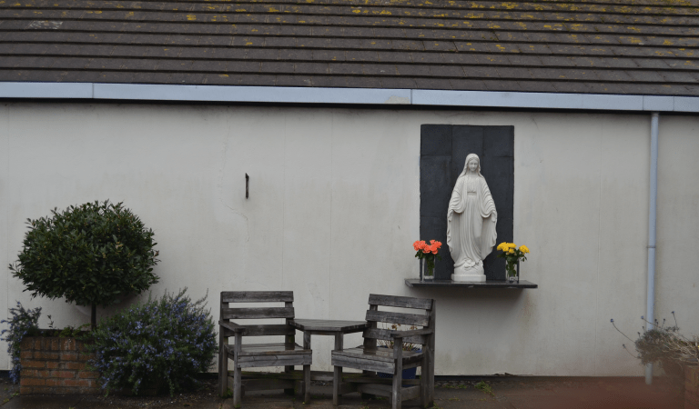 image of chairs and statue of the Virgin Mary outside white building