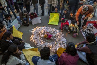 Mixed group of people seated in a circle around messages and candles.