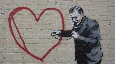 Graffiti of doctor holding stethescope to a big heart