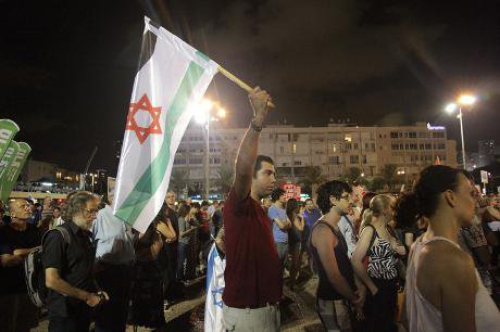 Peace demonstrator in Tel Aviv holds up Israeli flag in Palestinian colours