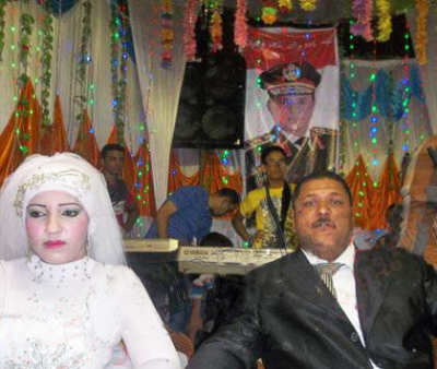 Bride and groom sit together, the man in front of a Sisi poster