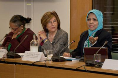 Three women sit behind a long desk, one addressing the audience.