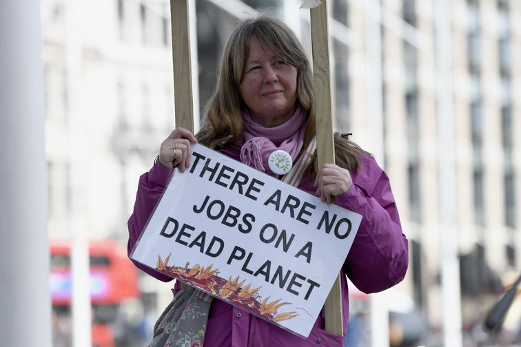 "Anti-fracking protester holding placard reading ""There are no jobs on a dead planet"""