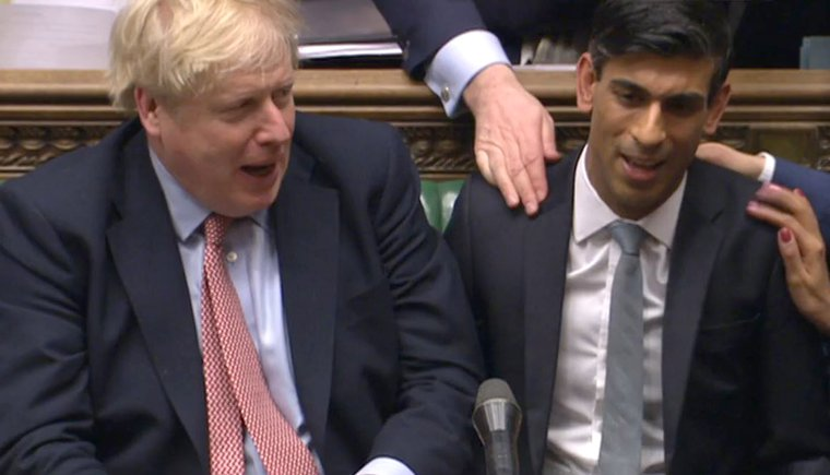 Chancellor Rishi Sunak next to Boris Johnson, being patted by MPs behind him in the House of Commons