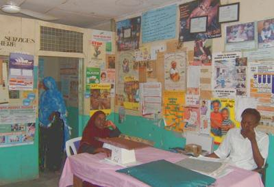 Photo of room covered with health posters with two people sitting at a table.
