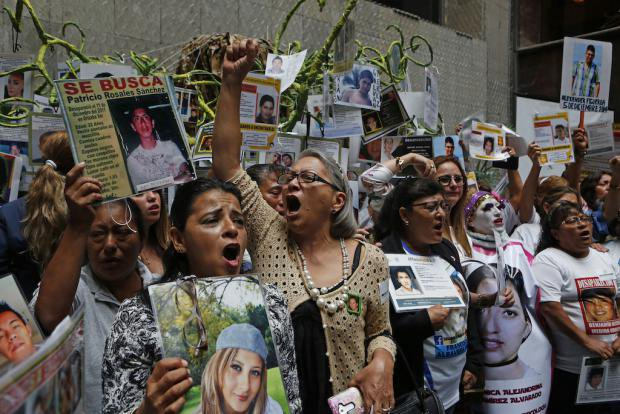 Women with photos of their children who disappeared in 2014 (Ayotzinapa)