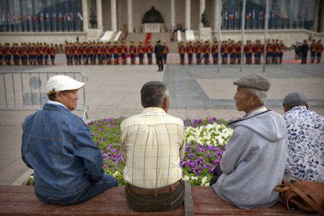 Men watch a parade by the Mongolian National Guard. Photo: Mark Schiefelbein/ AP/Press Association Images. All Rights Reserved