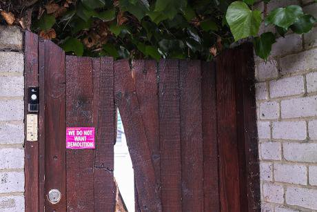 lead Wooden gate with pink sticker. Sticker reads