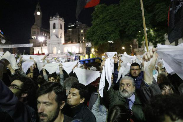 Crowds hold up white headscarves in a protest against the 2x1 law in Argentina