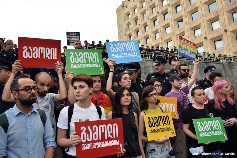 LGBT rights activists in Tbilisi hold signs with messages including 'Come out for equality' and 'Come out for freedom'.