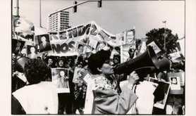 Black and white photo of street protest. Woman with megaphone and photograph, banners and placards in background..