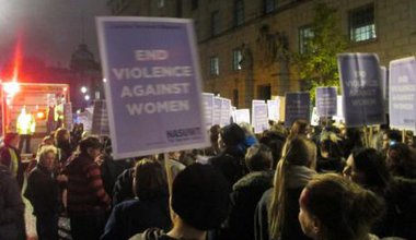 Women marching in the dark with an 'End Violence Against Women' placard visible