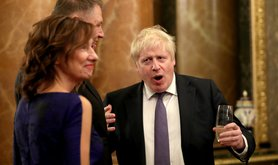 Prime Minister Boris Johnson (right) talks to guests during a reception at Buckingham Palac