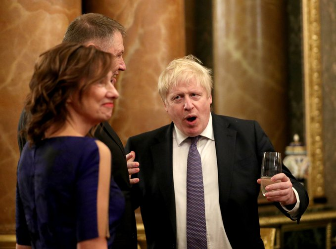 Prime Minister Boris Johnson (right) talks to guests during a reception at Buckingham Palace