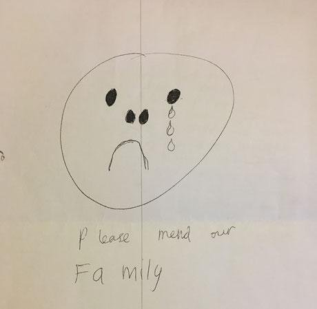 Child's drawing of a sad face with caption, please mend our family.