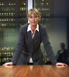 Business woman in board room, hands on table, staring out confidently