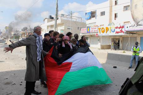 Palestinians stand in defiance. Emilie Baujard/Demotix. All rights reserved.