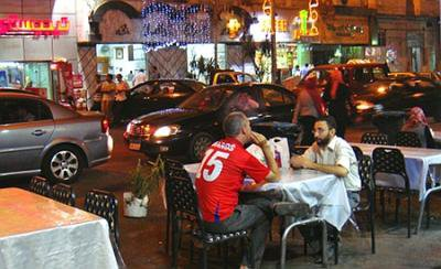 Night scene: cafe tables and chairs encroach into a Cairo street. Two men sit chatting.