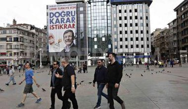 People walk by Turkish PM billboard.