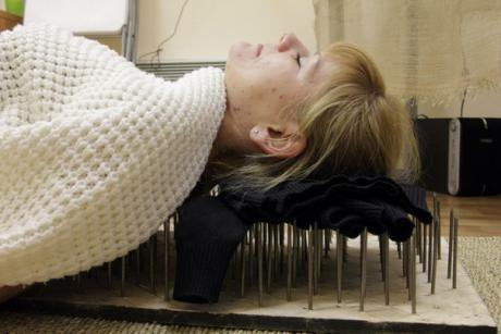 A woman lies on top of a bed of nails in the Alten Centre