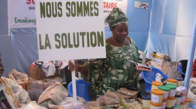 Woman holding a sign in french 'Nous sommes la solution