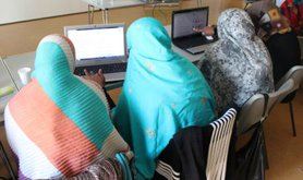 Three women sitting at computers, backs to camera