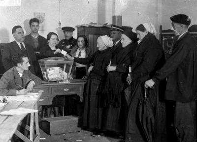 Black and white archive image of 1930s polling station with 4 women lined up to vote.